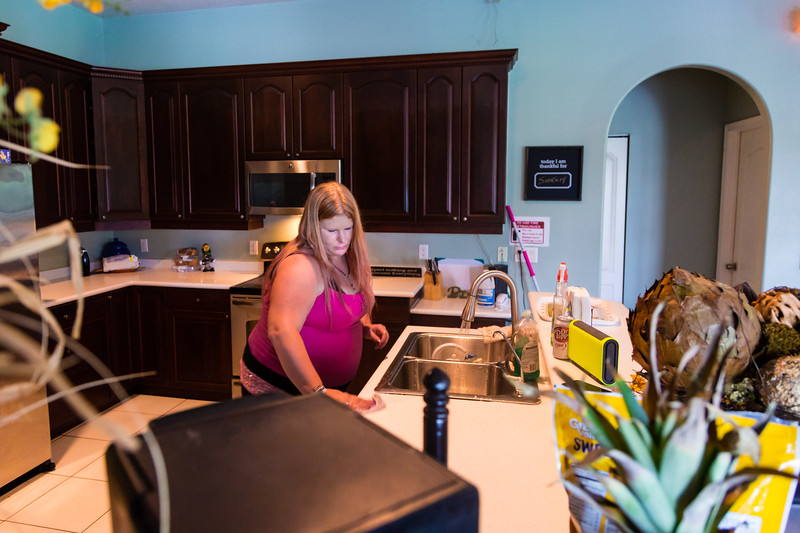 """Tabitha Franks, 31, of Loxahatchee, Florida, cleans the kitchen counter at the All About Recovery younger women's sober home in Loxahatchee, Florida on Friday, June 24, 2016. Residents are required to keep the sober home clean, but once a week, the residents  are assigned an area of the sober house to """"deep clean"""". (Joseph Forzano / The Palm Beach Post)"""