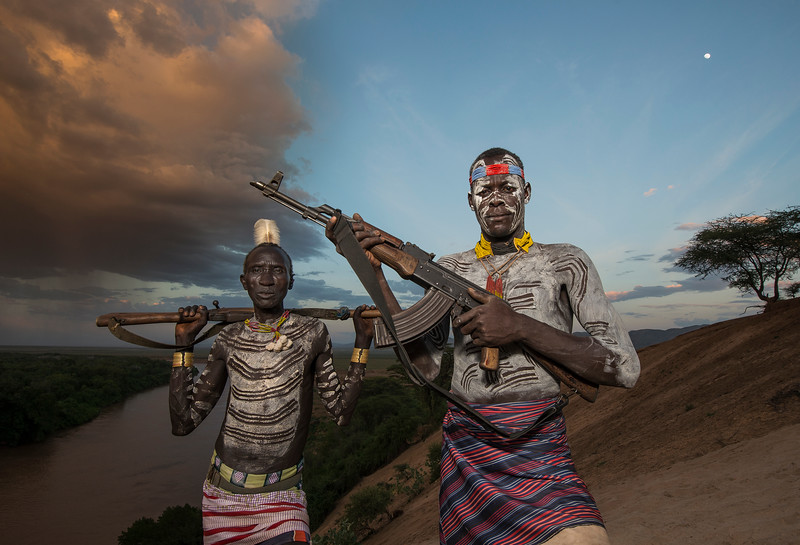 Two Karo men holding weapons which they use for protection from other tribes. The Nyangatom tribe is considered a constant threat by the Karo.  Omo Valley, Ethiopia, 2017