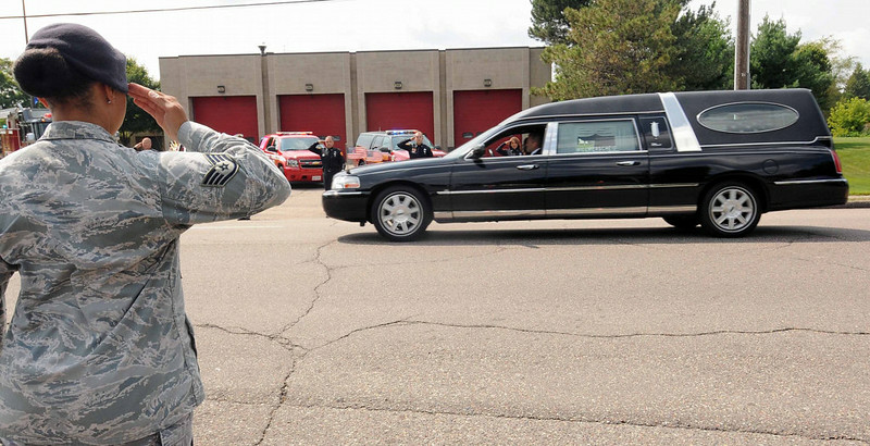 . U. S. Air Force staff sergeant Gerita Glenn salutes as the hearse bearing officer Patrick passes the Mendota Heights Fire Department station at 2121 Dodd Road.  (Pioneer Press: Scott Takushi)