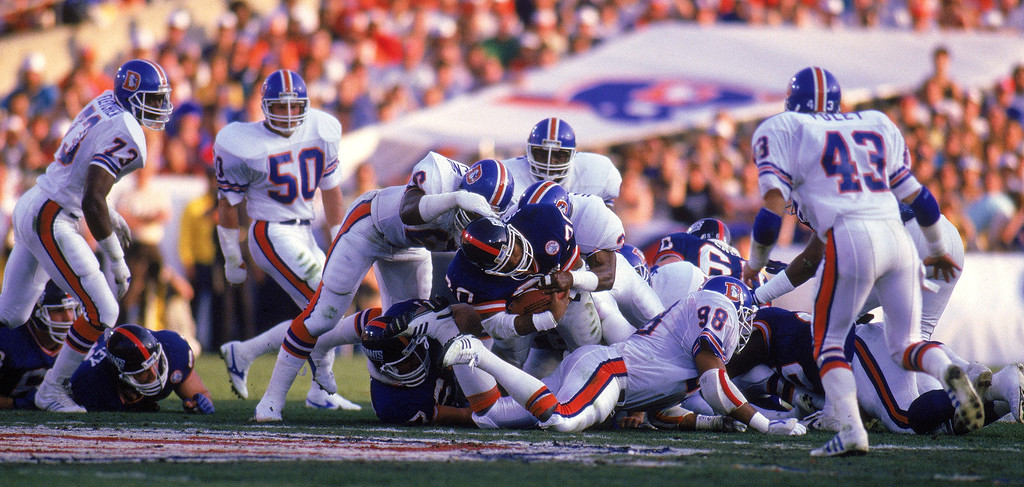 . Running back Joe Morris #20 of the New York Giants gets taken down by the Denver Broncos defense during Super Bowl XXI at the Rose Bowl on January 25, 1987 in Pasadena, California.  (Photo by Rick Stewart/Getty Images)