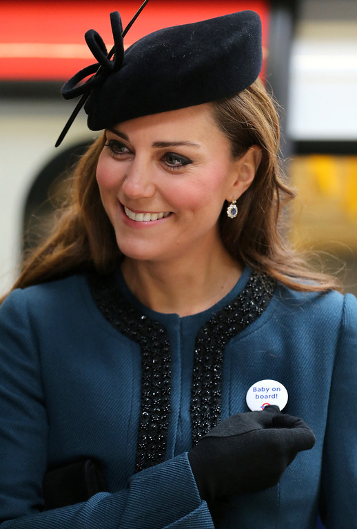 """. Britain\'s Catherine, Duchess of Cambridge, wears a Transport For London (TFL) badge that reads \""""baby on board\"""", given to her during a visit to Baker Street tube station with Queen Elizabeth II and Prince Philip, Duke of Edinburgh, in London on March 20, 2013 to mark 150th anniversary of the London underground. The 86-year-old queen attended her first public engagement for more than a week after she had to cancel a number of events last week as she was still recovering from a bout of gastroenteritis which saw her admitted to hospital on March 3 for the first time in ten years.  Chris Radburn/AFP/Getty Images"""