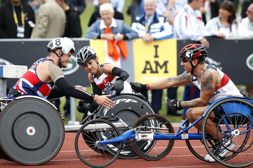 . Great Britain\'s Joseph Townsend (L) is congratulated by other competitors after winning the 1500m men wheel IT4 during the athletics event of the Invictus Games at Queen Elizabeth II Park in London on September 11, 2014. AFP PHOTO/ADRIAN DENNISADRIAN DENNIS/AFP/Getty Images