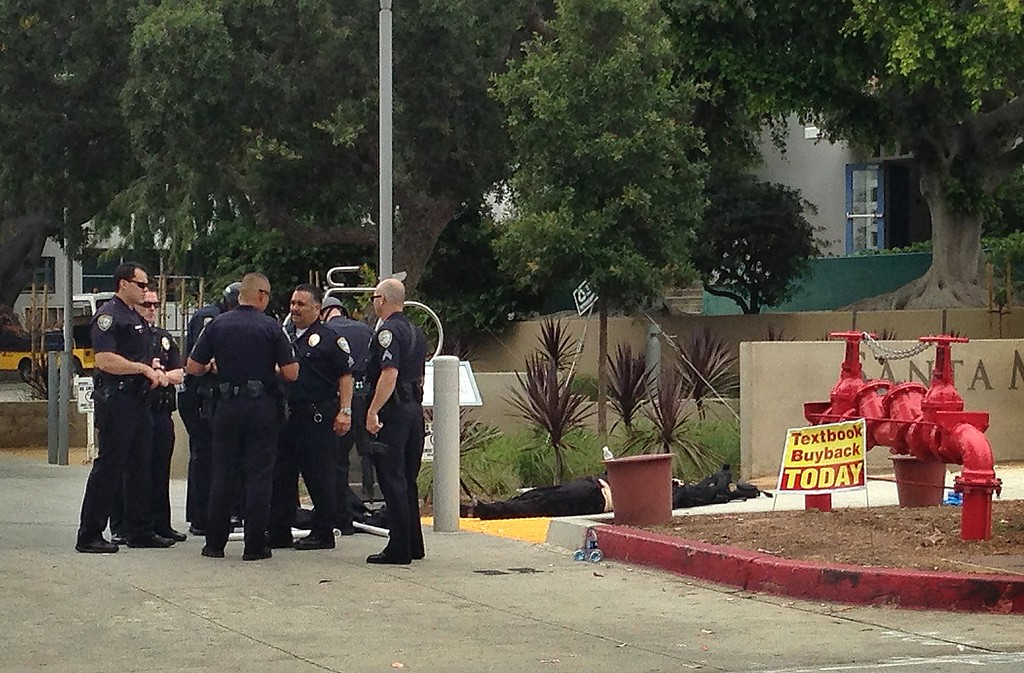 . Police officers stand next to a body near an entrance to Santa Monica College, Friday, June 7, 2013, in Santa Monica, Calif., following a shooting incident in the area.  Two people were found dead in a burned home near the college, where someone sprayed a street corner with gunfire, authorities said. (AP Photo/Tami Abdollah)