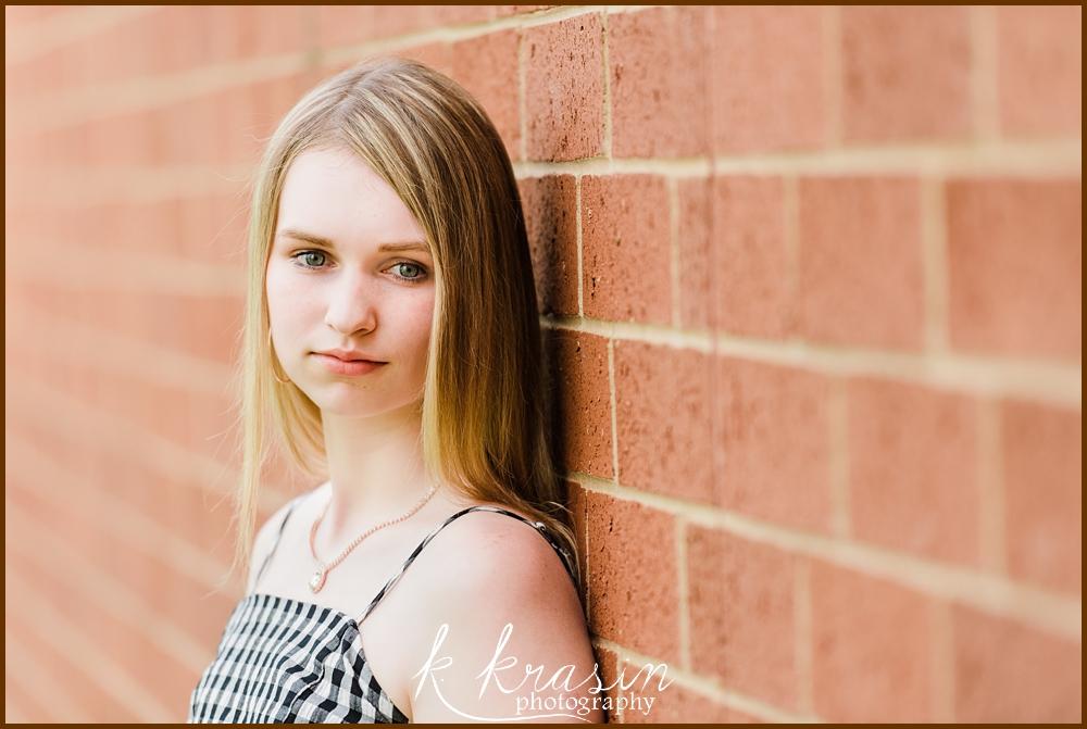 High school senior girl leaning on brick wall