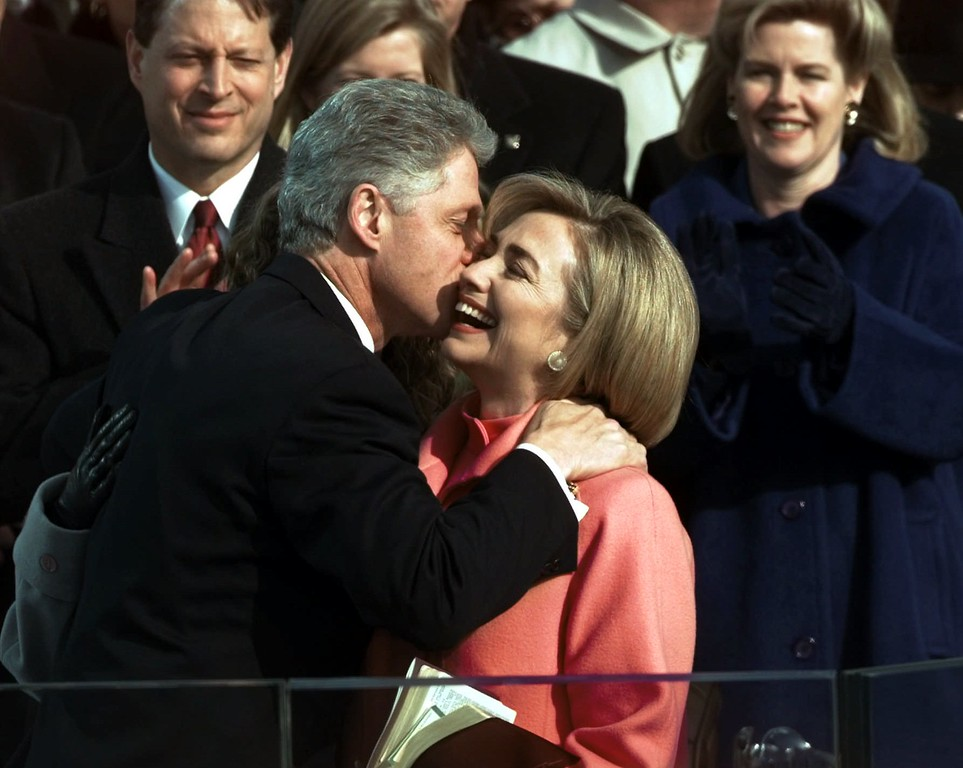 . President Clinton kisses his wife Hillary after he was sworn in for his second term by Supreme Court Chief Justice William Rehnquist during the 53rd Presidential Inauguration Monday, Jan. 20, 1997, in Washington. Vice President Al Gore and his wife Tipper are in the background. (AP Photo/Doug Mills)