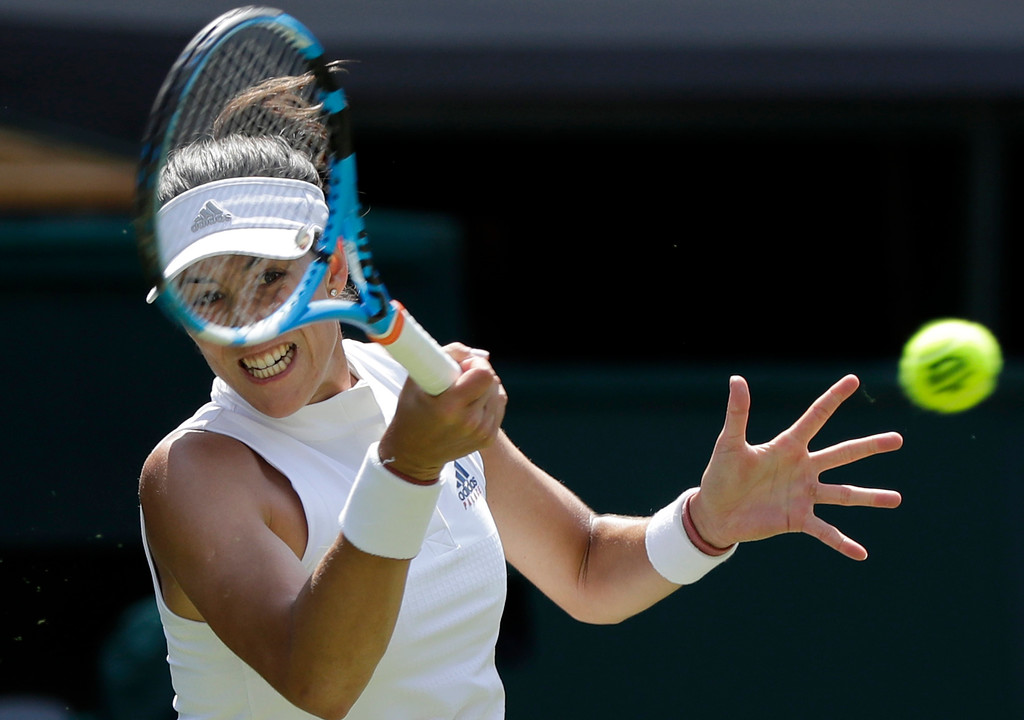. Garbine Muguruza of Spain returns the ball to Britain\'s Naomi Broady during their women\'s singles match on the second day at the Wimbledon Tennis Championships in London, Tuesday July 3, 2018. (AP Photo/Ben Curtis)