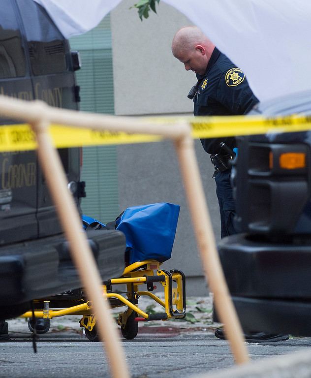 . A sheriff\'s deputy prepares to move the body of a person who died when a fifth floor balcony collapsed in Berkeley, Calif. on Tuesday, June 16, 2015. Berkeley police say several people are dead and others were  injured after the Library Gardens apartment balcony collapsed shortly before 1 a.m. near the University of California, Berkeley. (AP Photo/Noah Berger)