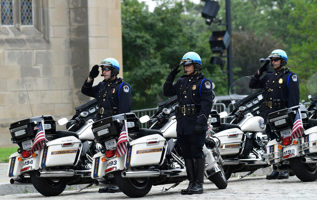 . Police officers salute as the casket of Sen. John McCain, R-Ariz., arrives at the Washington National Cathedral in Washington, Saturday, Sept. 1, 2018, for a memorial service. McCain died Aug. 25 from brain cancer at age 81. (AP Photo/Susan Walsh)