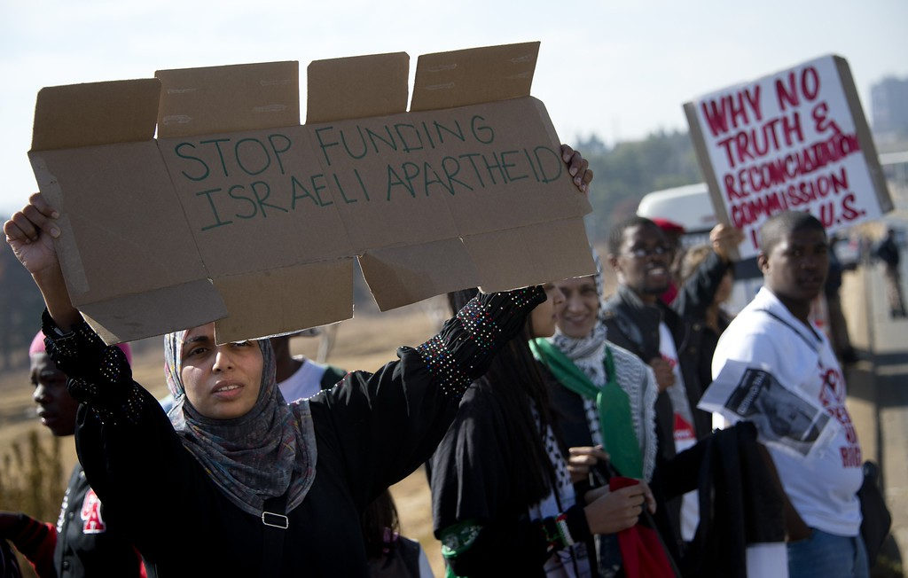 . A woman holds a sign during a protest against the US president\'s visit to South Africa outside the university in Soweto on June 29, 2013. Police fired stun grenades today at hundreds of protesters rallying against President Barack Obama\'s visit to South Africa. ODD ANDERSEN/AFP/Getty Images