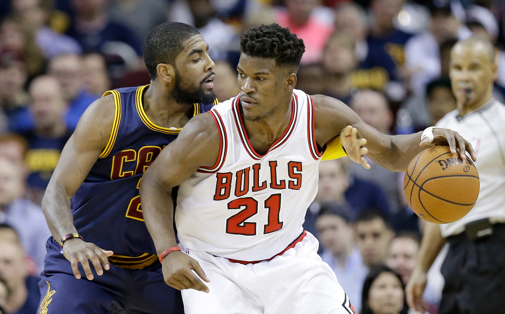 . Chicago Bulls\' Jimmy Butler (21) tries to get past Cleveland Cavaliers\' Kyrie Irving (2) during an NBA basketball game Sunday, April 5, 2015, in Cleveland. (AP Photo/Tony Dejak)