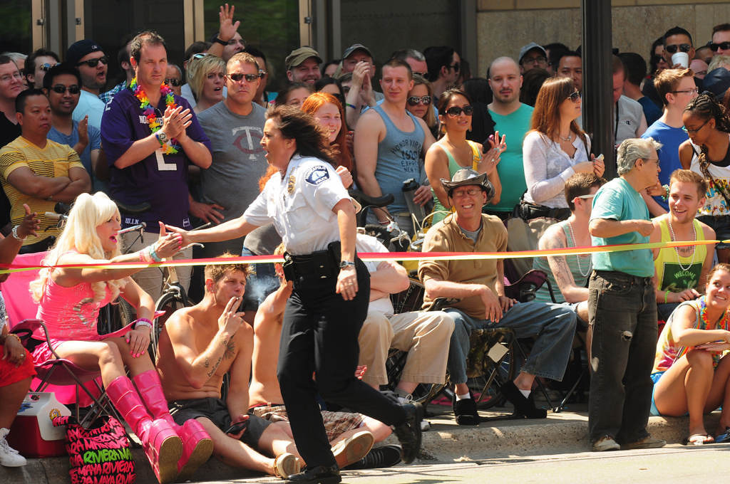 . Minneapolis Police Chief Janee Harteau runs along the parade route, slapping hands, during the annual Twin Cities Pride Parade. (Pioneer Press: Scott Takushi)