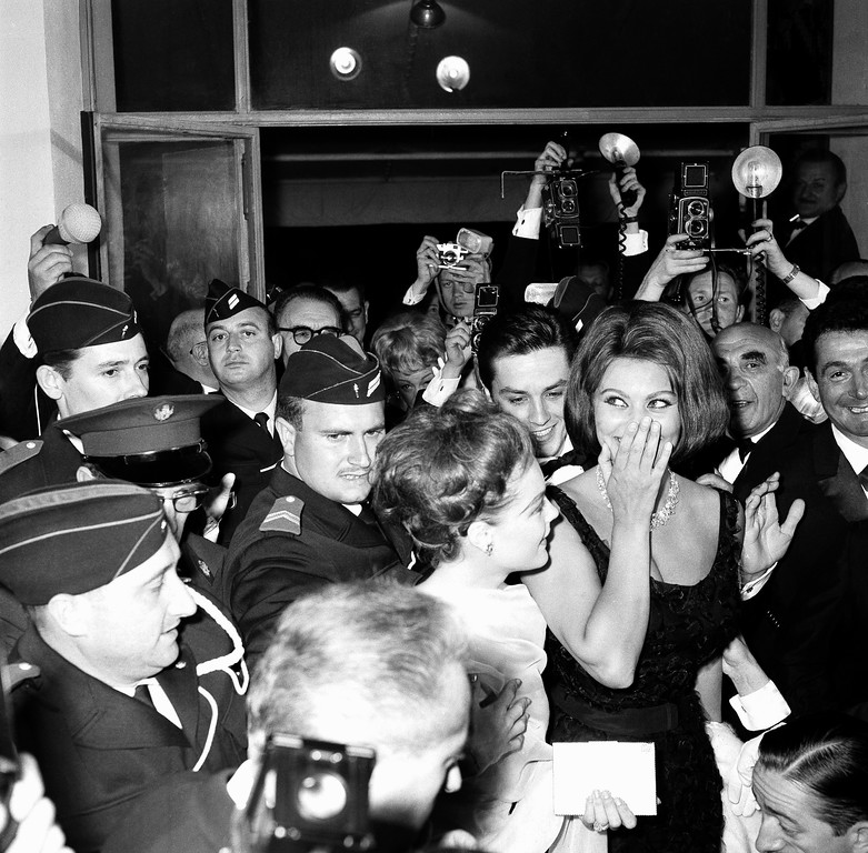 . Italian Oscar-winning actress Sophia Loren, extreme right, and her company are protected by police from crushing crowds as they arrive at Festival Palace for the opening of the Cannes film festival, May 7, 1962. Next to Miss Loren is actress Romy Schneider and behind them is actor Alain Delon. (AP Photo/H. Babout)