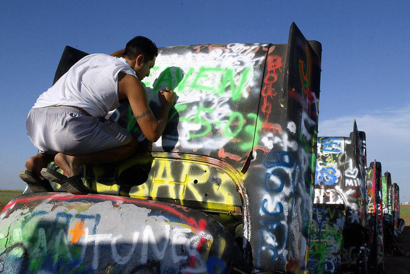". Visitor Ronny Davila from Tampa, Florida adds his graffiti to a car at ""Cadillac Ranch\"" on historic Route 66  in Amarillo, 06 July 2003. As a tribute to America\'s relationship with one of it\'s favorite automobiles, a collective of artists called Ant Farm  in 1974 placed 10 Cadillacs, ranging from a 1949 Club Coupe to a 1963 Sedan, in a wheat field located west of Amarillo.  Visitors are encourage to draw or paint on the cars.  Cadillac Ranch is a popular stopping off point for tourists on historic Route 66 which stretches from Chicago to Los Angeles.  (AFP PHOTO / Robyn BECK)"