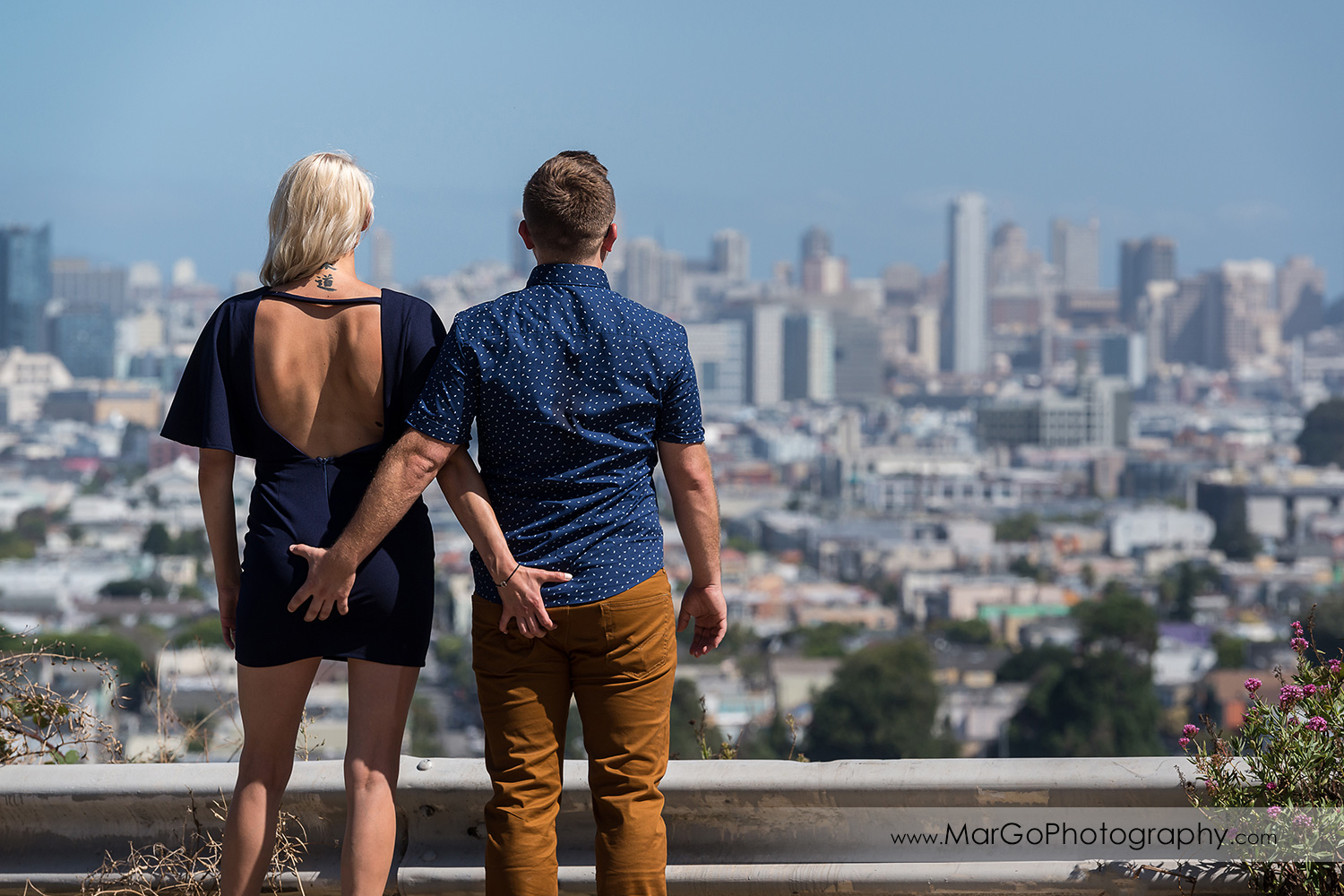 engagement session at Bernal Heights in San Francisco - rear view of cupule holding buts and looking at SF