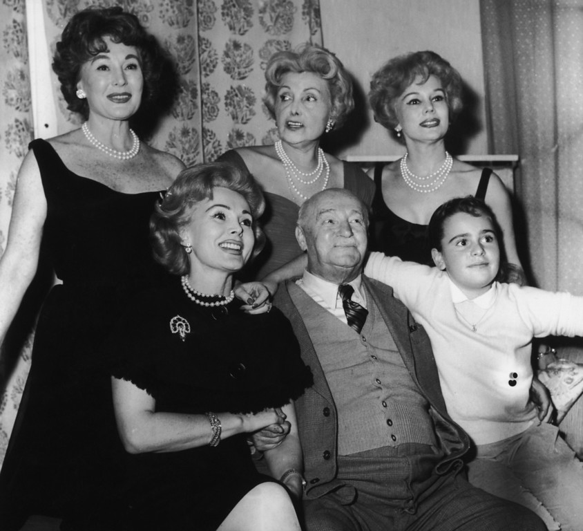 . Hungarian actress and socialite Zsa Zsa Gabor with her family at the Hotel Sacher in Vienna, October 1958. Standing, left to right, Zsa Zsa\'s sister, Magda (1915 - 1997), mother Jolie (1896 - 1997), and actress sister Eva (1919 - 1995). Seated, left to right; Zsa Zsa Gabor, her father, Vilmos and her daughter Constance Francesca Hilton. (Photo by Keystone/Hulton Archive/Getty Images)