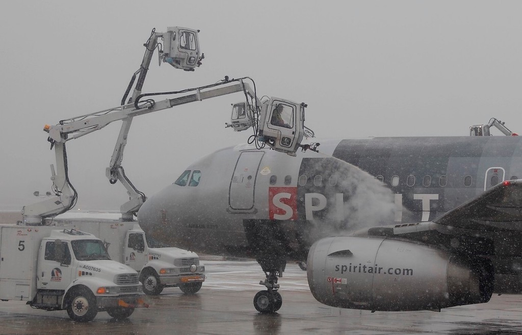 . As snow falls, workers de-ice a Spirit Air aircraft on the tarmac at Baltimore-Washington International Airport, in Baltimore, Md., Saturday, Jan. 7, 2017. Winter storms along the east coast have caused flight delays. (AP Photo/Carolyn Kaster)