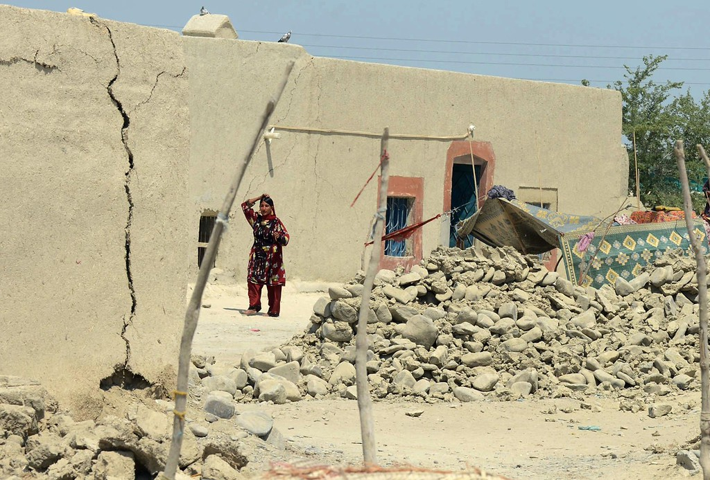 . A Pakistani earthquake survivor walks past collapsed mud houses at Labach area, in the earthquake-devastated district of Awaran on September 26, 2013.  AFP PHOTO / Banaras KHAN/AFP/Getty Images