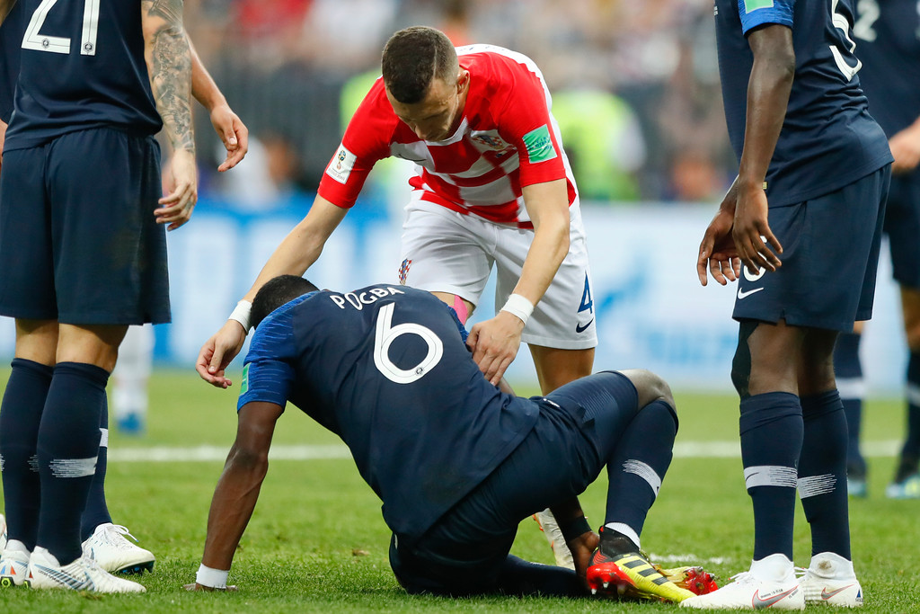 . Croatia\'s Ivan Perisic, top, helps France\'s Paul Pogba to stand up during the final match between France and Croatia at the 2018 soccer World Cup in the Luzhniki Stadium in Moscow, Russia, Sunday, July 15, 2018. (AP Photo/Matthias Schrader)