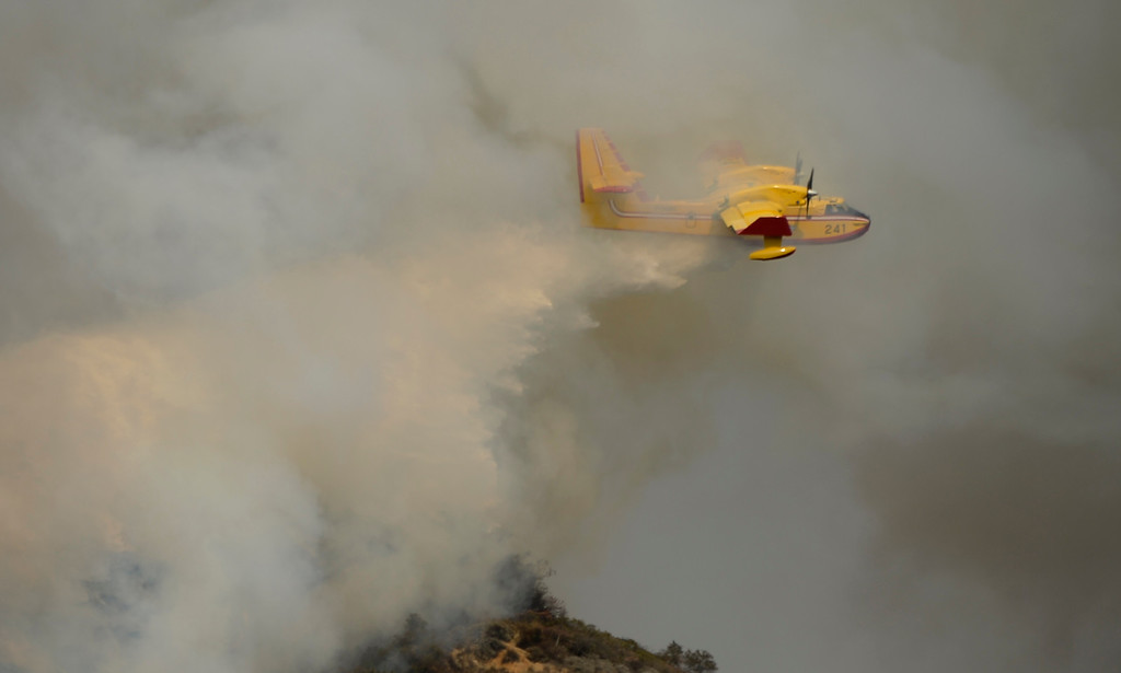 . A super scooper air tanker makes waters drops as  firefighters battle 2,200 plus acre brush fire that started the in early morning in the hills of Glendora Thursday. The fire destroyed six structors and 3 people taken into custody for involvement of starting the fire. Glendora California January 16,2014.