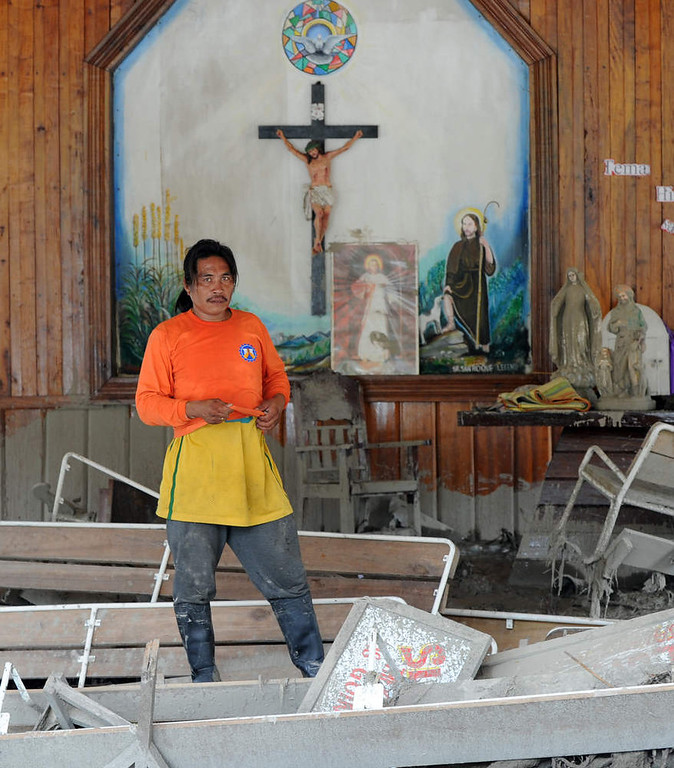 . A rescue worker stands inside a church littered with debris swept in by flash floods caused by Typhoon Bopha in the village of Andap in the town of New Bataan in Compostela Valley province on December 8, 2012.  Hungry and homeless typhoon survivors appealed for help on December 8 as the ravaged southern Philippines mourned its more than 500 dead and desperate people in one hard-hit town looted shops in search of food.     AFP PHOTO / TED  ALJIBE/AFP/Getty Images