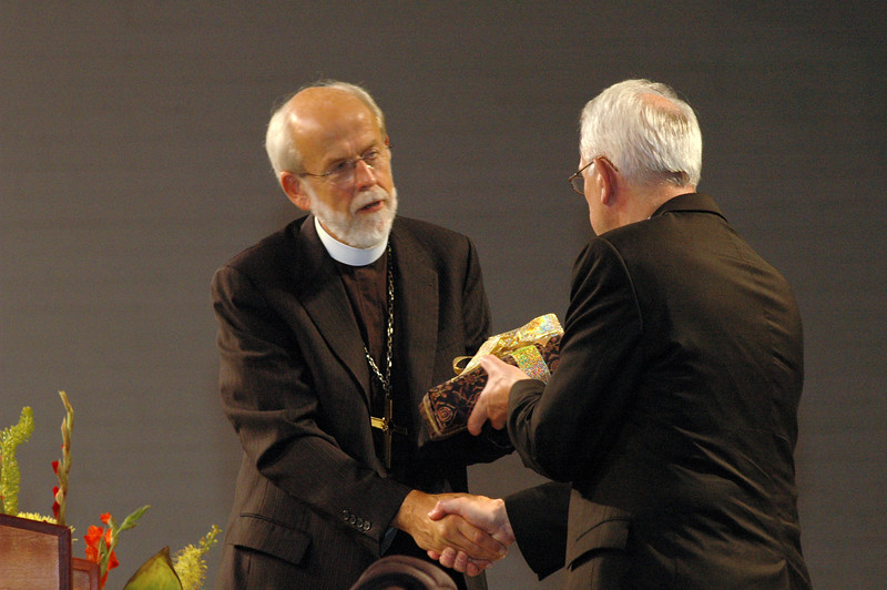 The Rev. Mark S. Hanson presents the Rev. Lowell G. Almen with a specially bound book containing messages from hundreds of his colleagues and friends.