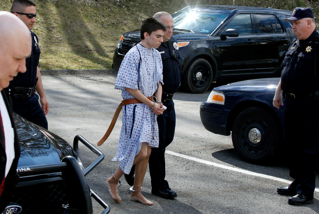 Description of . Alex Hribal, the suspect in the multiple stabbings at the Franklin Regional High School in Murrysville, Pa., is escorted by police to a district magistrate to be arraigned on Wednesday, April 9, 2014, in Export, Pa. Authorities say Hribal has been charged with allegedly stabbing and slashing 19 students and a police officer in the crowded halls of his suburban Pittsburgh high school Wednesday. (AP Photo/Keith Srakocic)