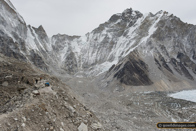 On the trail to base camp. Some trekkers navigate the lateral moraine of the Khumbu glacier, with some tents at base camp visible near the tip of theicefall, mid-right.