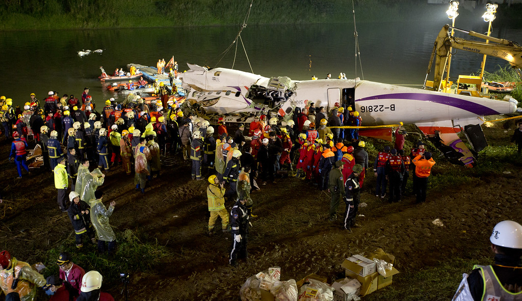 . Rescuers check the wreckage of the TransAsia ATR 72-600 on the Keelung river at New Taipei City on February 4, 2015. At least 23 people were killed when a passenger plane operated by TransAsia Airways clipped an overpass soon after take-off and plunged into a river in Taiwan, the airline\'s second crash in seven months.   (Photo by Ashley Pon/Getty Images)