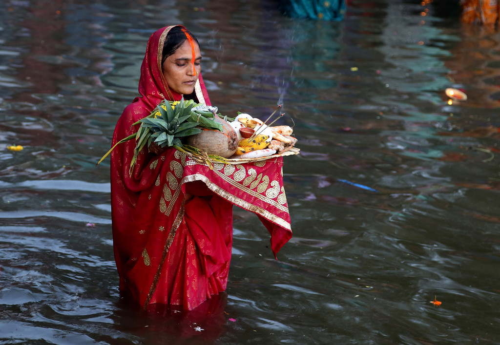 . A Hindu devotee stands in water and performs rituals to the setting sun during Chhath Puja festival in Bangalore, India, Friday, Nov. 8, 2013.  (AP Photo/Aijaz Rahi)