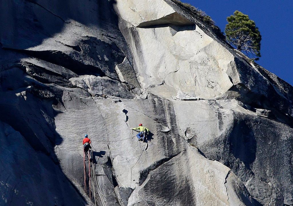 . Kevin Jorgeson, left, and Tommy Caldwell climb El Capitan, Wednesday, Jan. 14, 2015, as seen from the valley floor in Yosemite National Park, Calif. Caldwell and Jorgeson became the first to free-climb the rock formation\'s Dawn Wall. They used ropes and safety harnesses to catch them in case of a fall, but relied entirely on their own strength and dexterity to ascend by grasping cracks as thin as razor blades and as small as dimes. (AP Photo/Ben Margot)