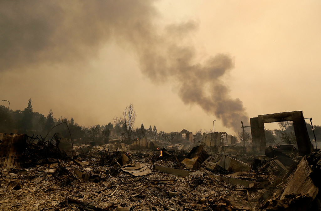 . Smoke rises over burned down homes in Santa Rosa, Calif., Monday, Oct. 9, 2017. Wildfires whipped by powerful winds swept through Northern California early Monday, sending residents on a headlong flight to safety through smoke and flames as homes burned. (AP Photo/Jeff Chiu)
