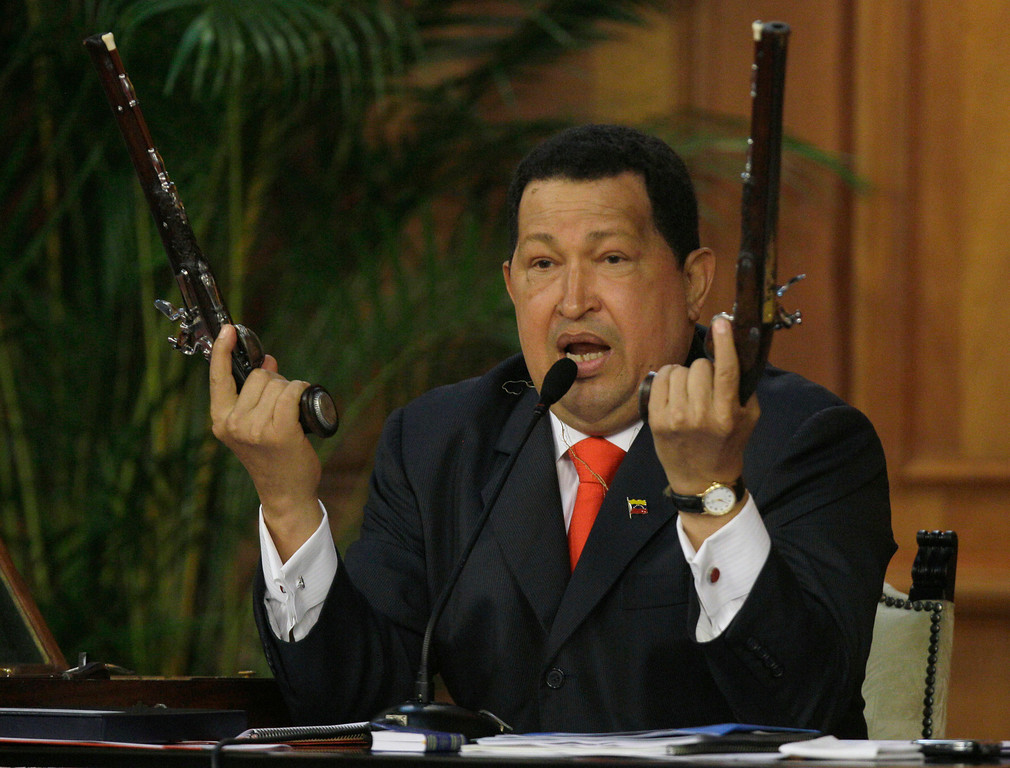 . In this July 24, 2012 file photo, Venezuela\'s President Hugo Chavez holds up a pair of pistols that he says belonged to Venezuela\'s independence hero Simon Bolivar during a ceremony marking 229th anniversary of Bolivar\'s birth at Miraflores presidential palace in Caracas, Venezuela.  Bolivar is the namesake of Chavez\'s Bolivarian Revolution movement, and his government is putting the finishing touches on a new mausoleum to house Bolivar\'s remains. (AP Photo/Fernando Llano, File)