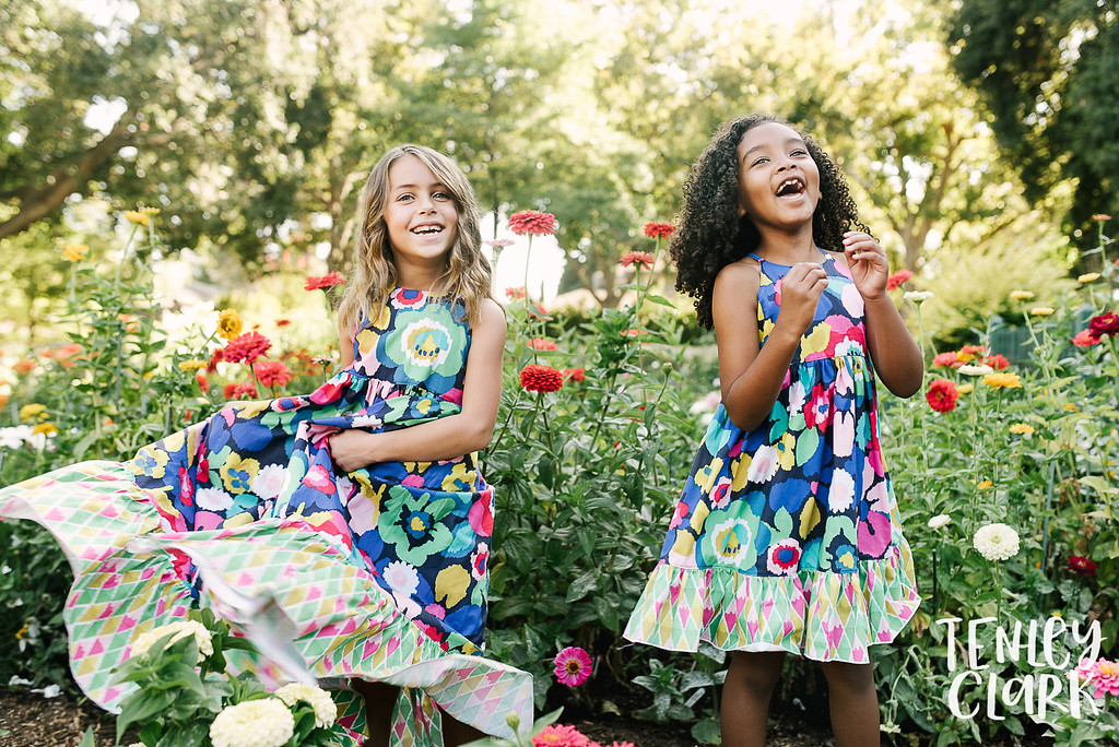 Playful kids fashion editorial-style commercial brand shoot with two girls playing in a garden for Gold Magnolia kids clothing boutique by Tenley Clark Photography. Models: Sofia and Olivia.