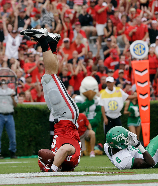 . Georgia tight end Arthur Lynch (88) flps on his head after scoring on a touchdown on a pass from quarterback Aaron Murray as North Texas defensive back Hilbert Jackson (6) defends in the first half of an NCAA college football game Saturday, Sept. 21, 2013 in Athens, Ga. (AP Photo/John Bazemore)
