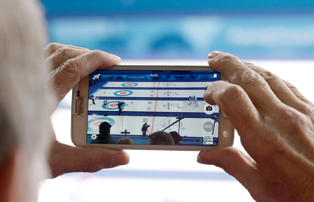 . A man records the men\'s curling finals match between United States and Japan at the 2018 Winter Olympics in Gangneung, South Korea, Saturday, Feb. 24, 2018. United States won the gold. (AP Photo/Aaron Favila)