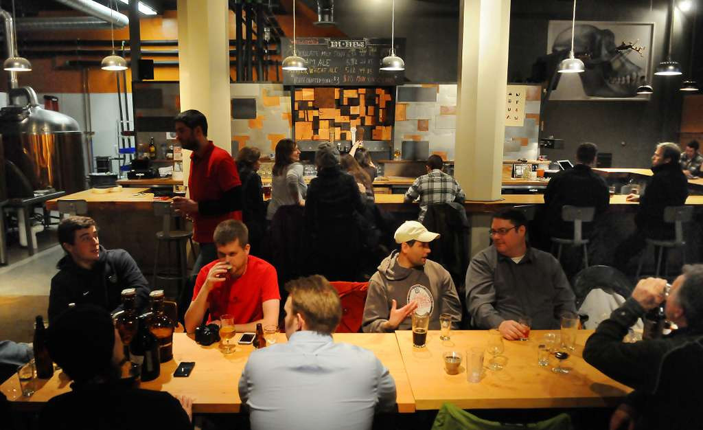 . Dangerous Man Brewing in Minneapolis: Craft-beer enthusiasts line a long table and bar at the copper-and-stainless-steel taproom of the Northeast Minneapolis brewery on March 5, 2013. (Pioneer Press: John Autey)