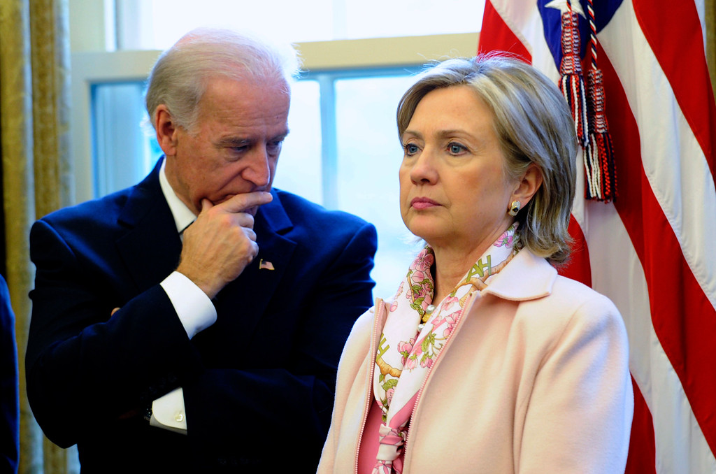 . FILE - In this Dec. 7, 2009 file photo, then-Secretary of State Hillary Rodham Clinton stands with Vice President Joe Biden in the Oval Office of the White House in Washington.   (AP Photo/Susan Walsh, File)