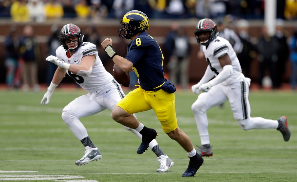 . Michigan quarterback John O\'Korn (8) scrambles during the first half of an NCAA college football game against Ohio State, Saturday, Nov. 25, 2017, in Ann Arbor, Mich. (AP Photo/Carlos Osorio)