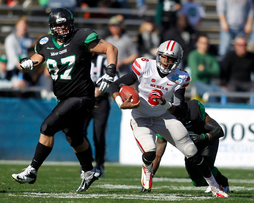 . UNLV quarterback Caleb Herring (8) eludes the tackle attempt by North Texas defensive back Marcus Trice (8) as defensive tackle Richard Abbe (97) trails the play during the first half of the Heart of Dallas NCAA college football game, Wednesday, Jan. 1, 2014, in Dallas. (AP Photo/Mike Stone)