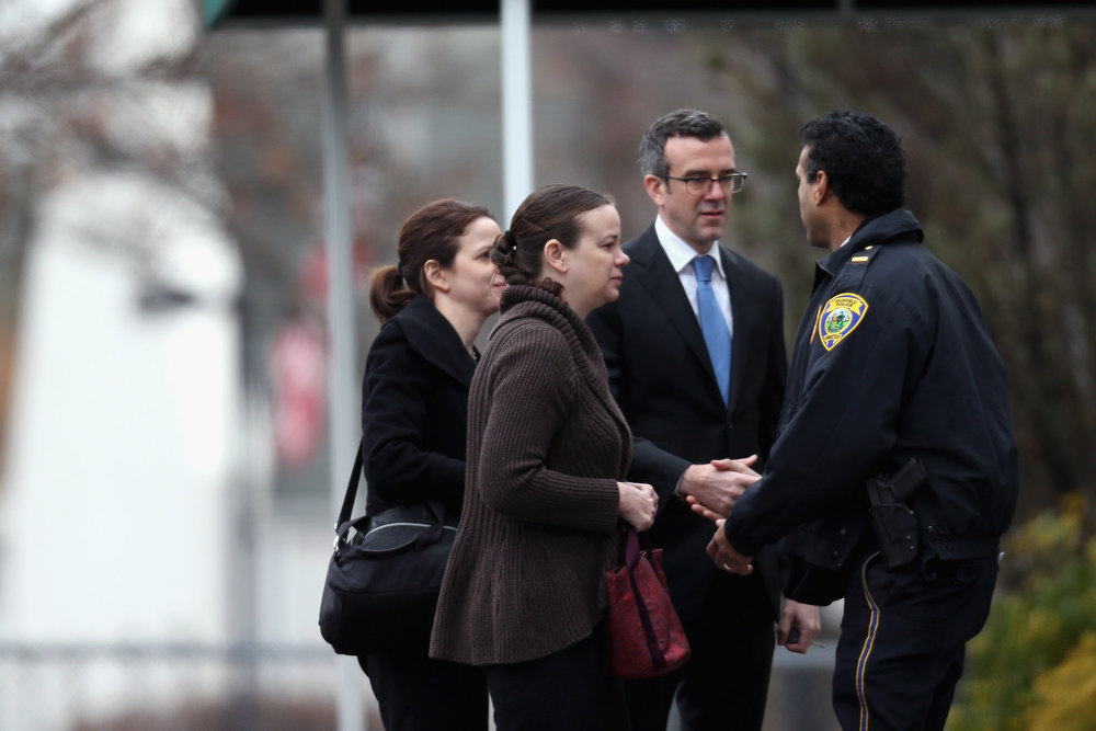 . People greet a police officer as they arrive for the funeral services of six year-old Noah Pozner, who was  killed in the shooting massacre in Newtown, CT, at Abraham L. Green and Son Funeral Home on December 17, 2012 in Fairfield, Connecticut. Today is the first day of funerals for some of the twenty children and seven adults who were killed by 20-year-old Adam Lanza on December 14, 2012.  (Photo by Spencer Platt/Getty Images)