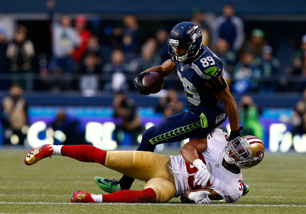 . Wide receiver Doug Baldwin #89 of the Seattle Seahawks with the ball after a catch against free safety Eric Reid #35 of the San Francisco 49ers in the first half during the 2014 NFC Championship at CenturyLink Field on January 19, 2014 in Seattle, Washington.  (Photo by Tom Pennington/Getty Images)
