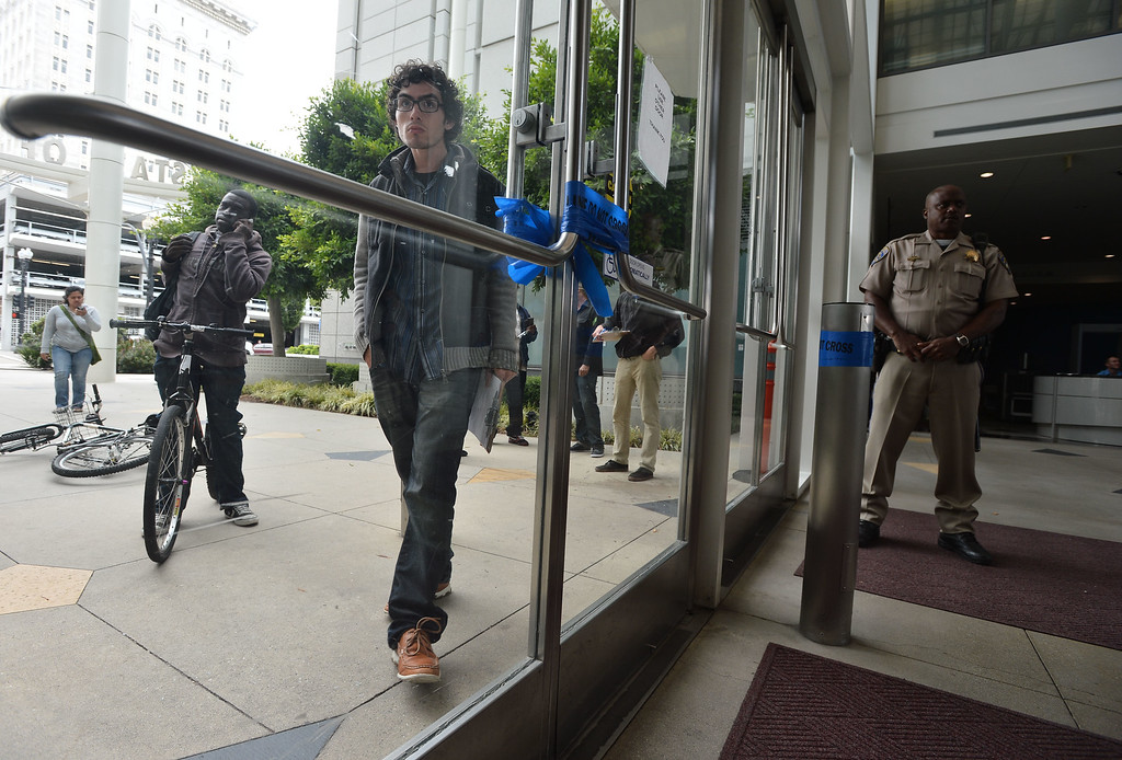 . Protesters gather outside the locked doors of the Elihu Harris State Building in downtown Oakland, Calif., on Monday, Aug. 5, 2013. Seven protesters were led from the scene in riot cuffs after staging a protest in solidarity with hunger strikers in California prisons. (Kristopher Skinner/Bay Area News Group)