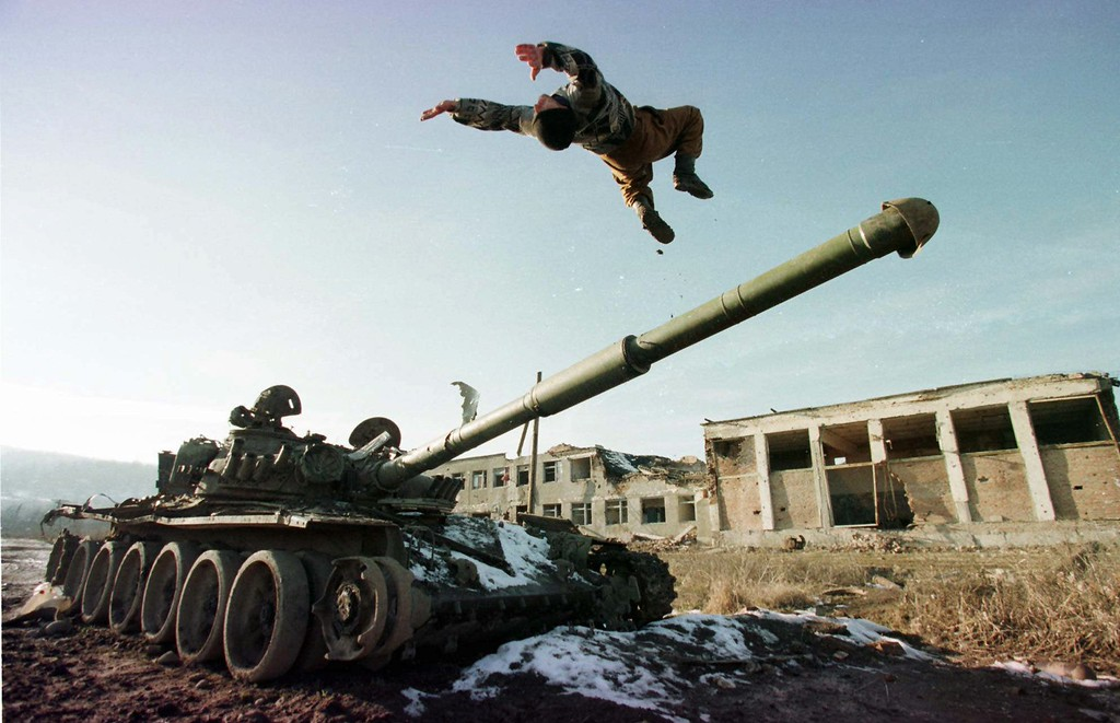 . A Chechen soldier does a back flip off a Russian tank gun in the Chechen village of Bamut Friday, Jan. 24, 1997. Elections are planned in Chechnya on Monday and the separatist leaders are campaigning to make Chechnya fully independent of Russia. (AP Photo/Sergei Karpukhin)