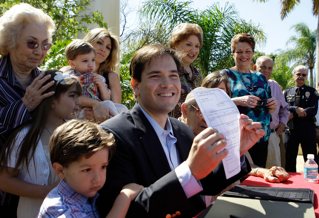. FILE - In this April 27, 2010 file photo, Marco Rubio, surrounded by family members, holds up a signed document declaring his candidacy in the Florida GOP primary for U.S. Senate in West Miami, Fla.  (AP Photo/Lynne Sladky, File)