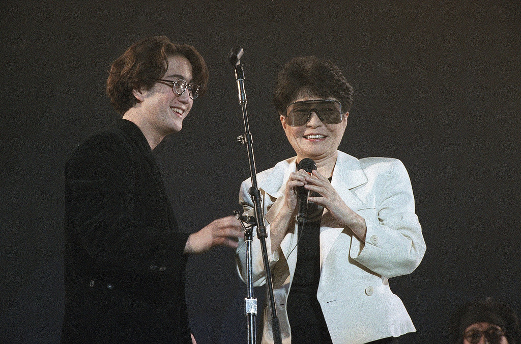 """. Yoko Ono and Sean Lennon,  widow and a son of John Lennon, tell the audience about John\'s life after the opening number \""""Power to the People\"""" during the \""""Greening of the World\""""  concert held in evening  on Friday, Dec. 21, 1990 at the Tokyo Dome to celebrate the 50th birthday of John Lennon.  (AP Photo/Tsugufumi Matsumoto)"""