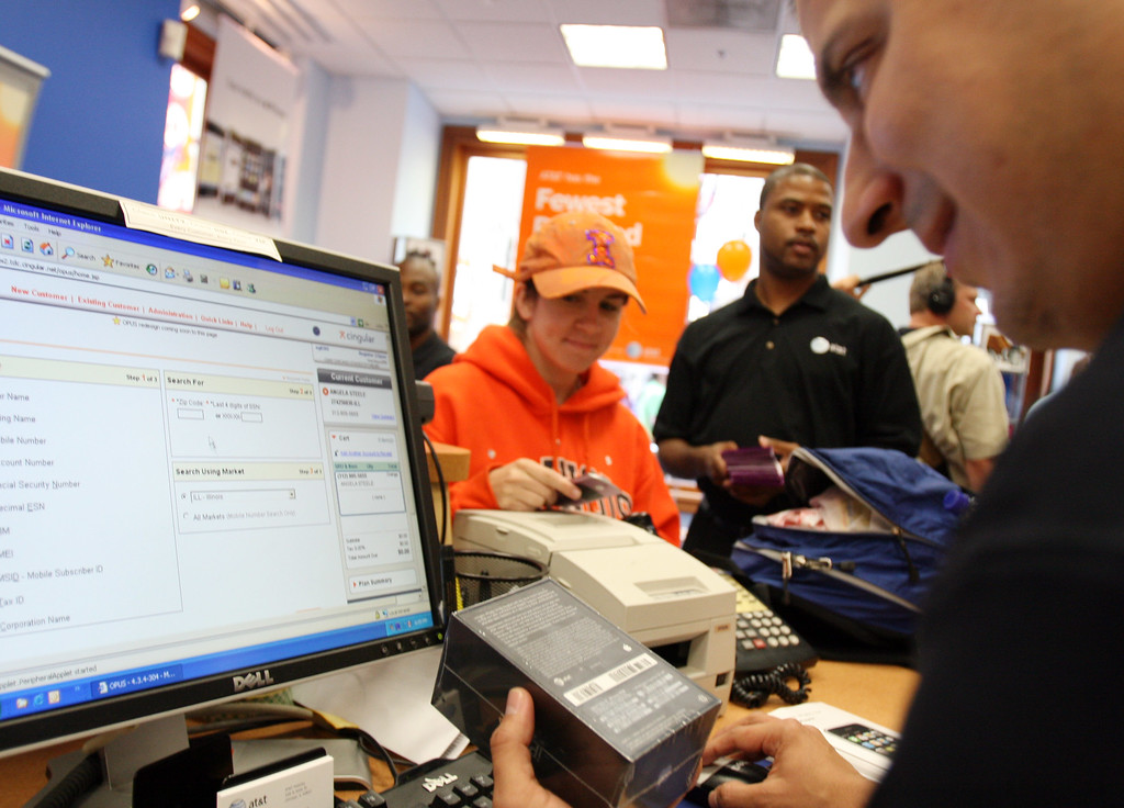 . Susan Lester, center, waits as AT&T Sales Associate, Eddie Garcia, right, rings up the new iPhone at the AT&T store in downtown Chicago, Friday, June 29, 2007. (AP Photo/ Stacie Freudenberg)