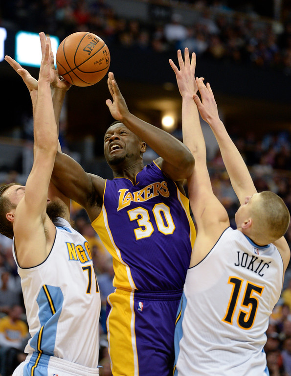 . DENVER, CO - MARCH 02: Los Angeles Lakers forward Julius Randle (30) battles through a double team by Denver Nuggets center Joffrey Lauvergne (77) and Denver Nuggets center Nikola Jokic (15) as he goes to the basket March 2, 2016 at Pepsi Center. (Photo By John Leyba/The Denver Post)