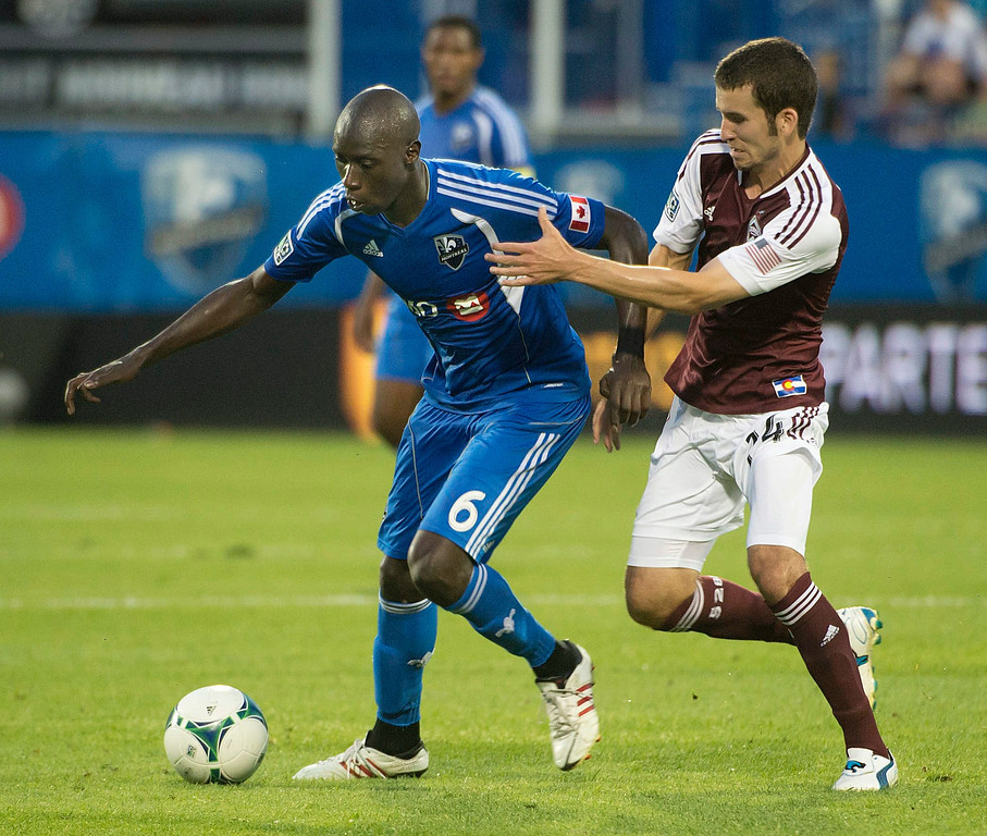 . Montreal Impact\'s Hassoun Camara is harassed by Colorado Rapids\' Nathan Sturgis during the second half of an MLS soccer game in Montreal on Saturday, June 29, 2013. (AP Photo/The Canadian Press, Peter McCabe)