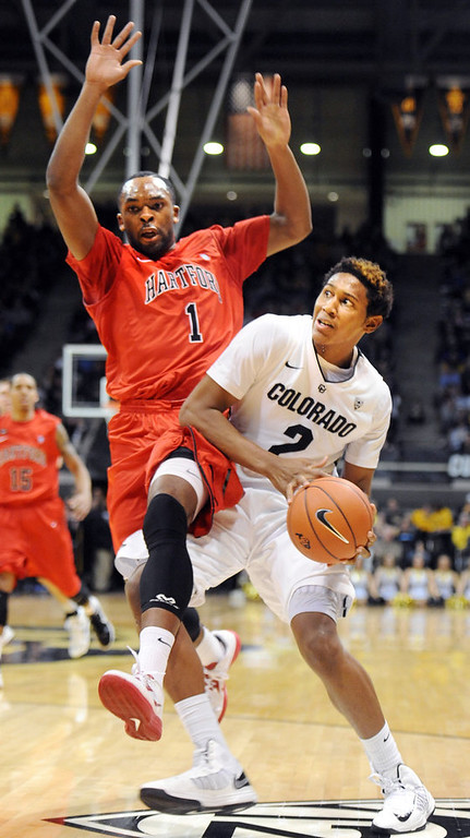 . Xavier Johnson of CU , drives on Wes Cole of Hartford, during the first half of the December 29, 2012 game in Boulder. (Cliff Grassmick / Daily Camera) December 29, 2012