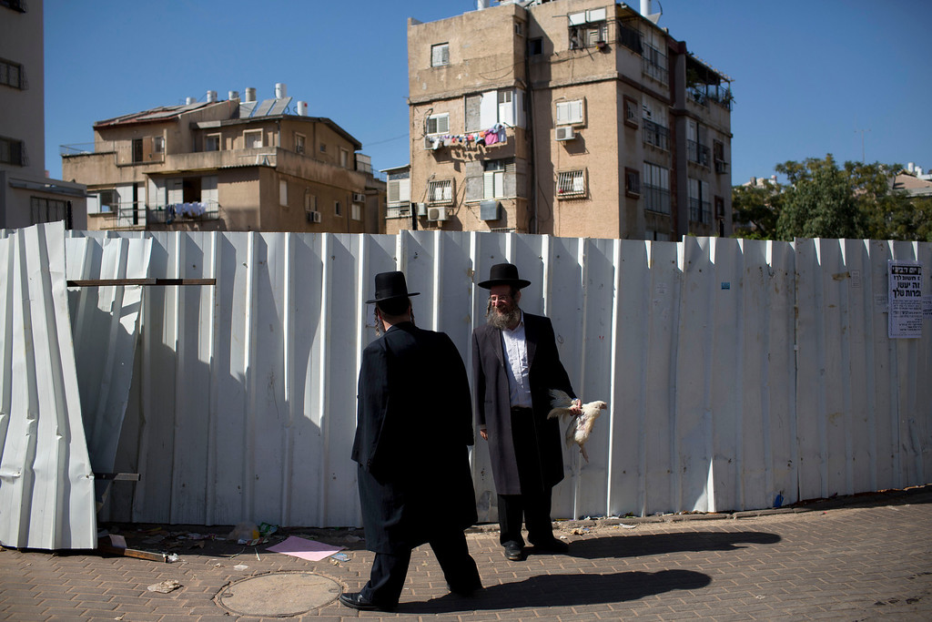 . An ultra-Orthodox Jewish man holds a chicken as part of the Kaparot ritual in the ultra-Orthodox city of Bnei Brak near Tel Aviv, Israel, Wednesday, Sept. 11, 2013. (AP Photo/Oded Balilty)